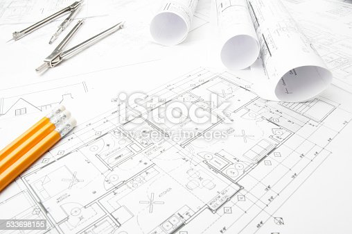 508818208 istock photo Architectural blueprints and blueprint rolls with drawing instruments 533698155