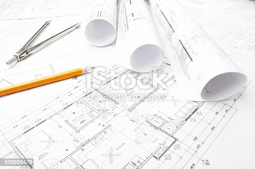 508818208 istock photo Architectural blueprints and blueprint rolls with drawing instruments 533959479