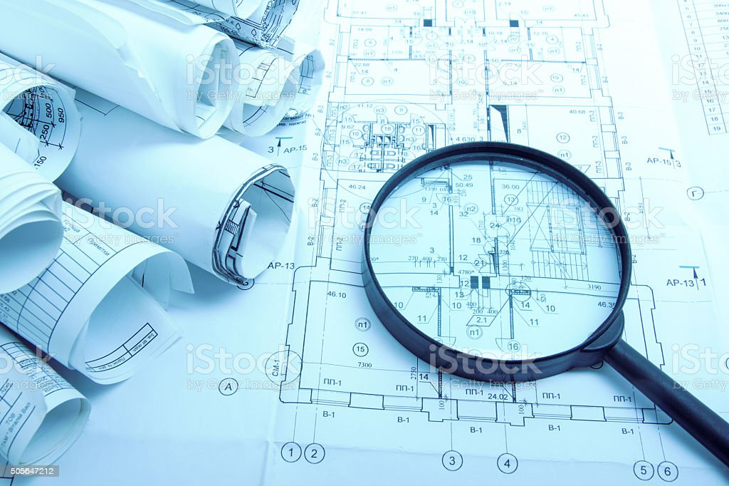 Architectural blueprints and blueprint rolls with magnifying glass architectural blueprints and blueprint rolls with magnifying glass royalty free stock photo malvernweather Image collections