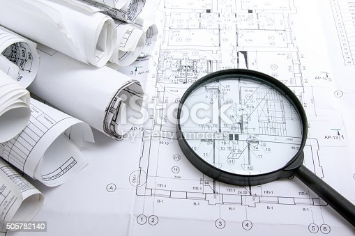 istock Architectural blueprints and blueprint rolls with magnifying glass 505782140