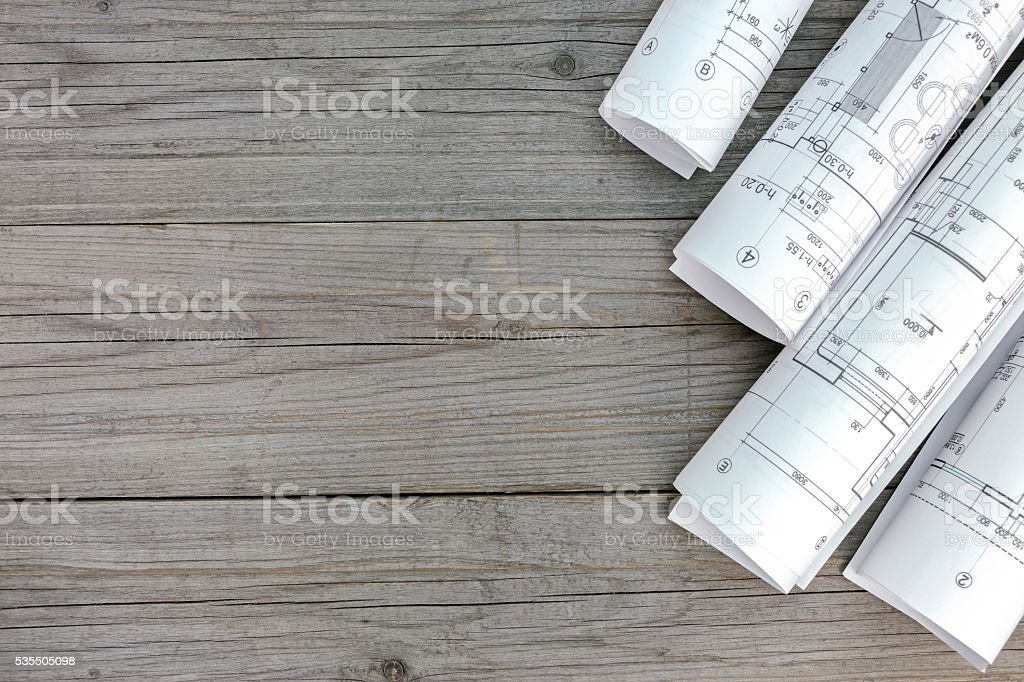 architectural blueprints and home plans on wooden background stock photo