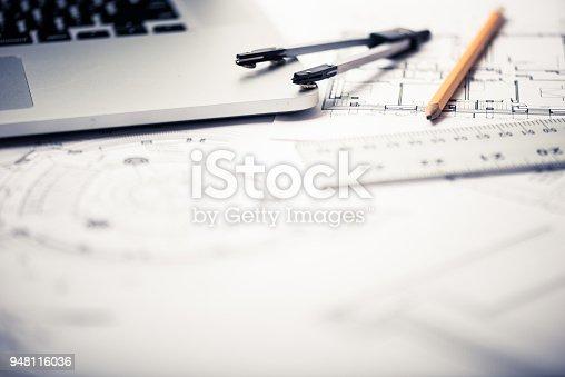 istock Architectural blueprints on architect's desk 948116036