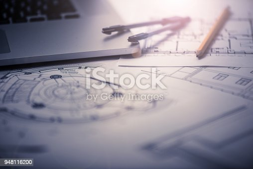 Background image showing architectural blueprints, drawing tools, and a laptop on architect's desk