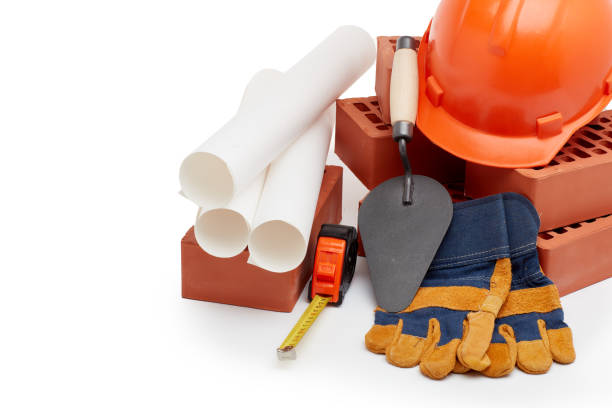Architectural blueprints, stack of bricks, masonry trowel,  construction hard hat on white background. Construction concept. stock photo