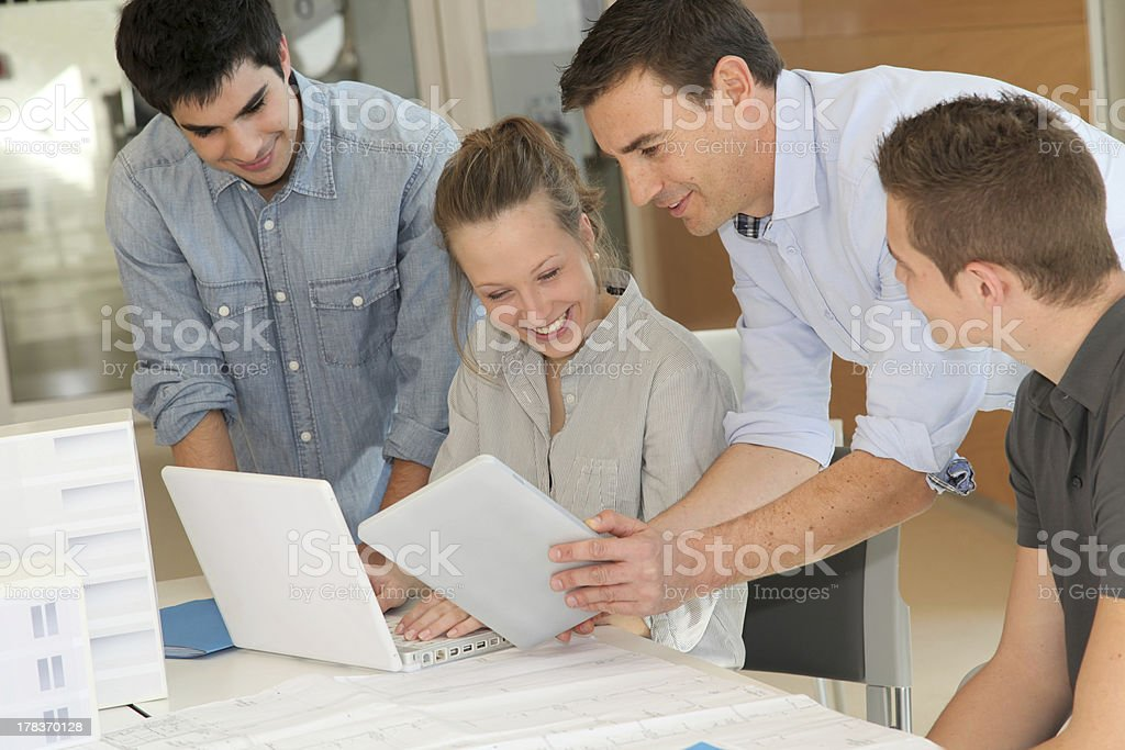 Architectural design students with tablets Educator with students in architecture working on electronic tablet Adult Stock Photo