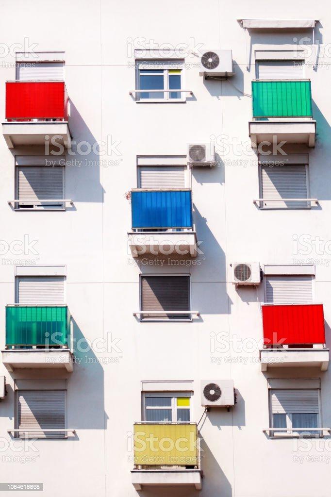 Detalhe arquitetônico e padrão de moderno edifício residencial com varandas coloridas e janelas dos apartamentos. Retrato de nova cidade urbana construção fachada com varandas de vidro de várias cores. - foto de acervo