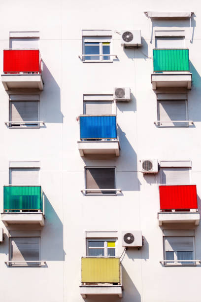 Architectural detail and pattern of modern residential building with colorful balconies and windows of apartments. Portrait of new urban city building facade with glass balconies of various colors. stock photo