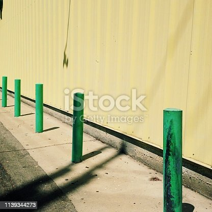 istock Architectural detail of green poles and cream wall 1139344273