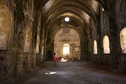 Muğla, Turkey-April 26, 2013: Architectural details from inside the ruins of the monastery in the ghost village of Kayaköy, abandoned many years ago. Young tourist woman examines the walls.