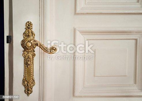 Antique interior doorknob on an old wooden door in Berlin, Germany.