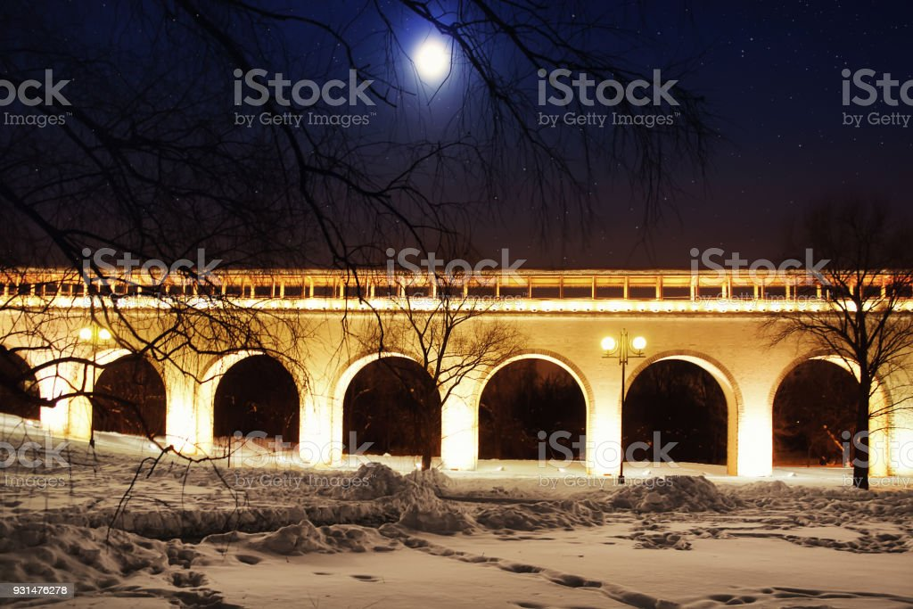Architectural monument. Beautiful aqueduct bridge in winter against the background of the starry sky with the moon stock photo
