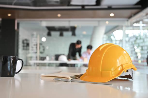 arkitektoniska office skrivbord byggprojekt med ritning utrustning och ingenjör hjälm. - arbetssäkerhet bildbanksfoton och bilder