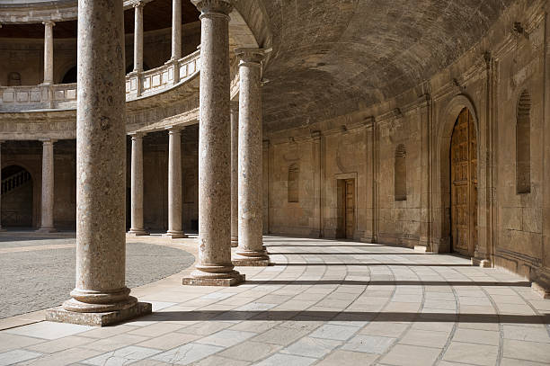 Architectural photo showing Alhambra Columns, Granada, Spain An interior view of The Palace of Charles V showing massive support columns, located within the Alhambra in Granada, Spain  palace of charles v stock pictures, royalty-free photos & images