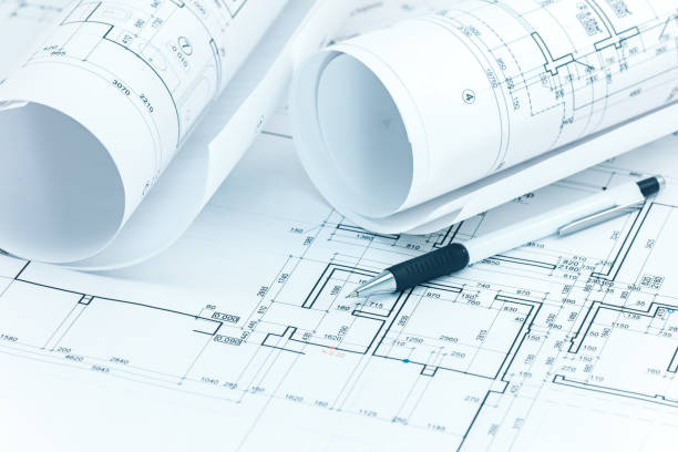 architectural plans, blueprint rolls and pencil on architect desk stock photo