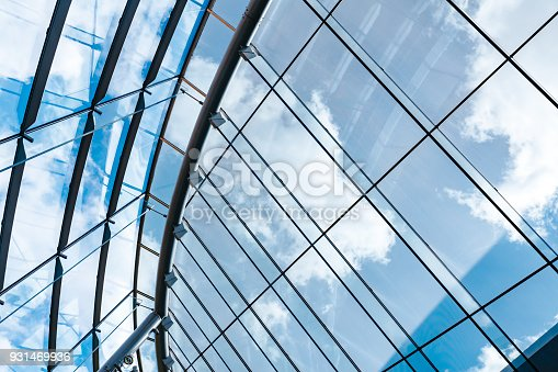 New modern building with glass roof looking up through glass house ceiling looking beautiful cloudy and sunny blue sky on spring day