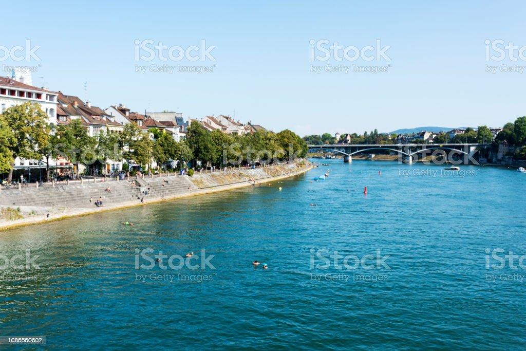 Architektur entlang Rhein mit Menschen sind Schwimmen und Sonnenbaden in Basel, Schweiz – Foto