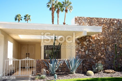 Front entrance and exterior view of mid century architecture. A main feature is the stone on the one wall.  Xeriscaped garden of cactus and succulents.