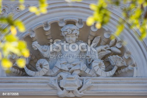 Old brown architecture detail with human and flowers