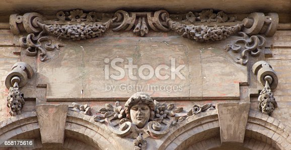 Brown architecture detail with a human head and flowers