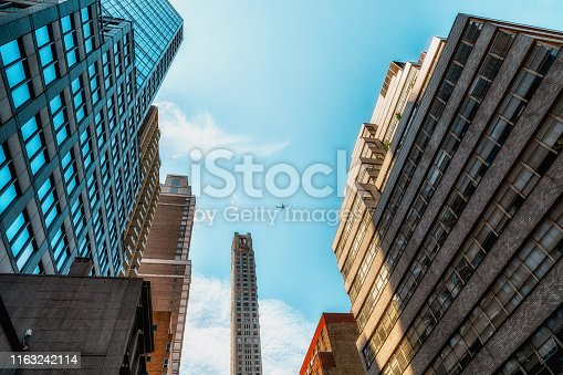 490774222istockphoto Architecture in New York City, Low Angle View, Vanishing Point, Blue Sky Background 1163242114