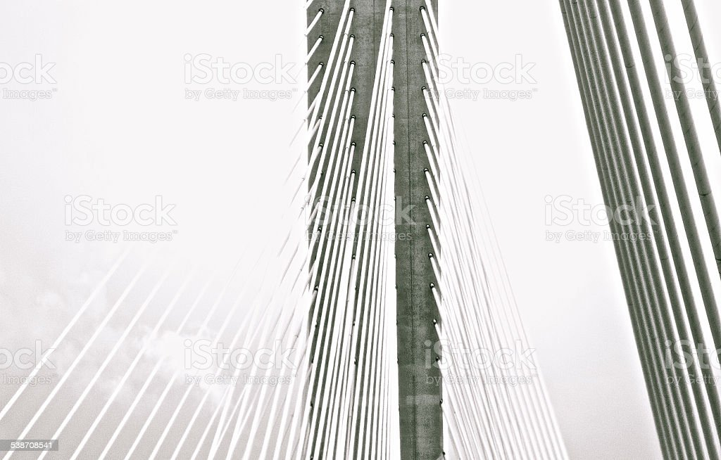 Suspension bridge held up with steel cables in black and...