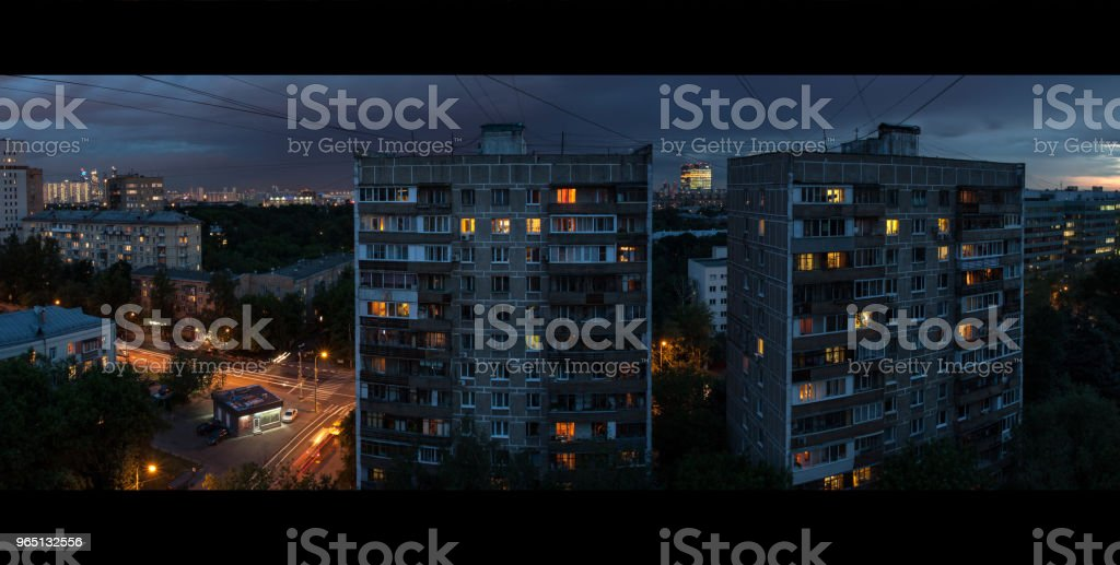 Architecture of the Soviet Union. Two tall houses on the street on March 8. View from the apartment window. Evening city after the rain. Lights up in the Windows zbiór zdjęć royalty-free
