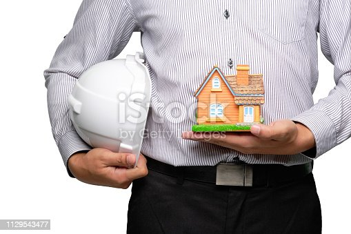 Crop image of engineer or architect holding home model and white plastic helmet. Clipping path.