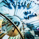 """""""Footprints on transparent glass spiral staircase down the glass elevator in futuristic building, unrecognizable people."""""""