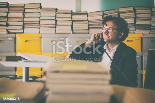 Middle aged businessman working in the archive. He talking on the phone in his office full of archive boxes and documents.