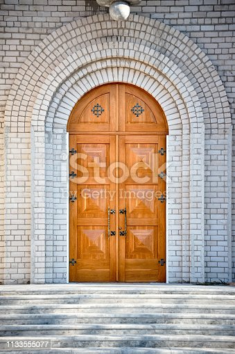 Archway entrance with golden oak doors to unfinished Church of the Beheading of St. John the Baptist  in European city Grodno or Hrodna Belarus.