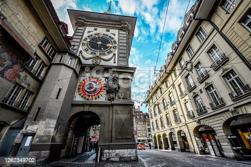 Bern Clocktower, Switzerland. The center of Bern near the Zytglogge clocktower architectural arch passage and cobbled streets. On the rights side there are marketplaces and on the left side is the clocktower itself.