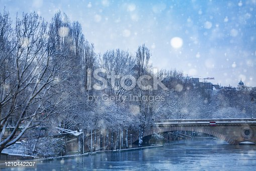 Pont d'Arcole during flood and snow covered trees in Paris downtown at cold winter day