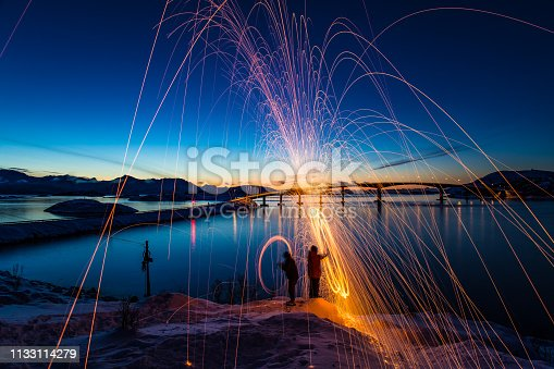 Scandinavian winter adventure light painting sparks spinning in Northern Norway Amazing Sommaroy Island sunset natural light and condition Northern Europe