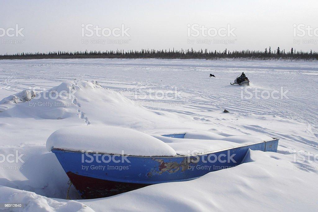 Arctic Blue Boat, Snowmobile & Dog stock photo