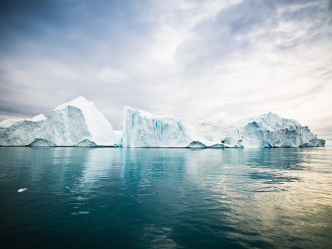 Huge Icebergs drifting in polar arctic icefjord at the west greenland coast. Ilulissat Icefjord, Greenland, North West Coast.