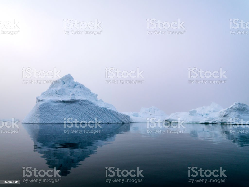 Arctic Icebergs in a foggy day on Arctic Ocean in Greenland. Climate...