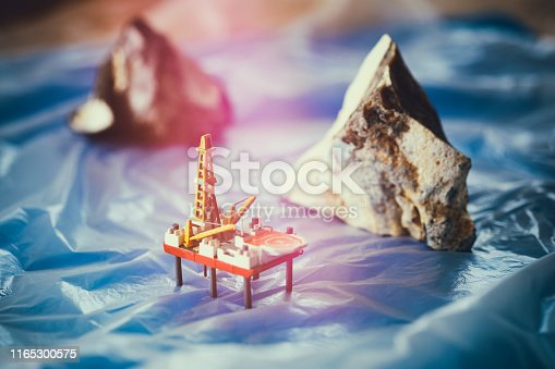 Tabletop shot with homemade model of a drilling platform and two flints