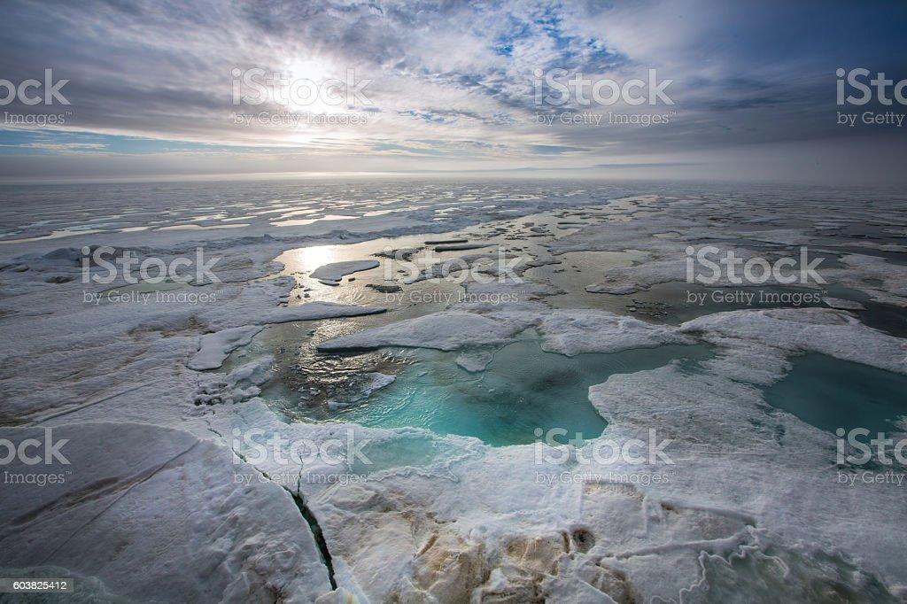 Arctic ocean with floating ice against sunset. stock photo