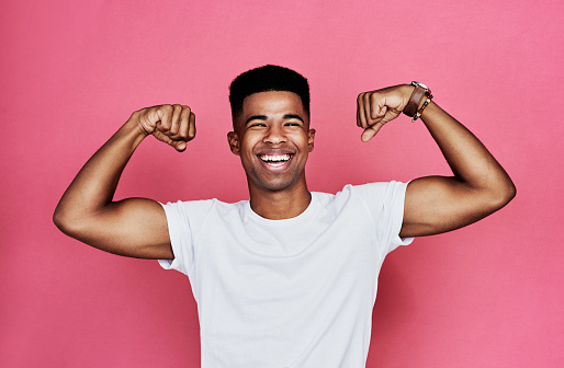 Cropped portrait of a handsome young man standing alone and flexing his biceps against a pink background in the studio