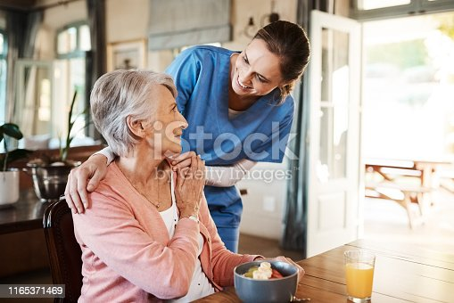 Shot of a young nurse checking up on a senior woman during breakfast at a nursing home