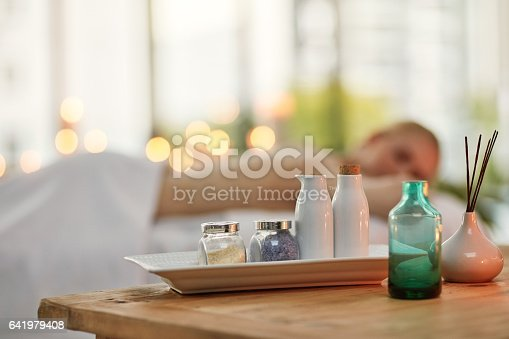 Cropped shot of various pampering essentials in a spa with a young woman in the background