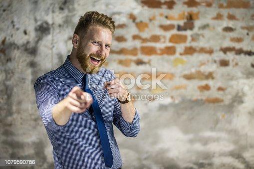 Happy redhead man aiming at camera while looking at it. Copy space.