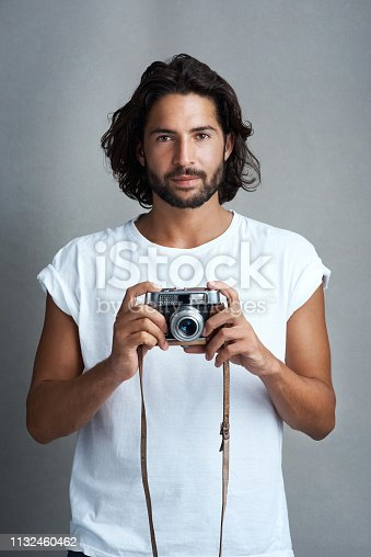 Studio portrait of a young man posing with a vintage camera against a grey background