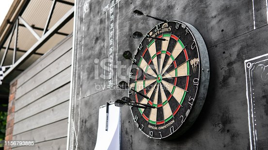 area for playing darts with a sheet of glasses on a black background. Darts and darts scoreboards