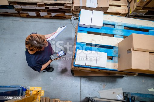 istock Areal view of woman amidst pallets in warehouse 1053843900