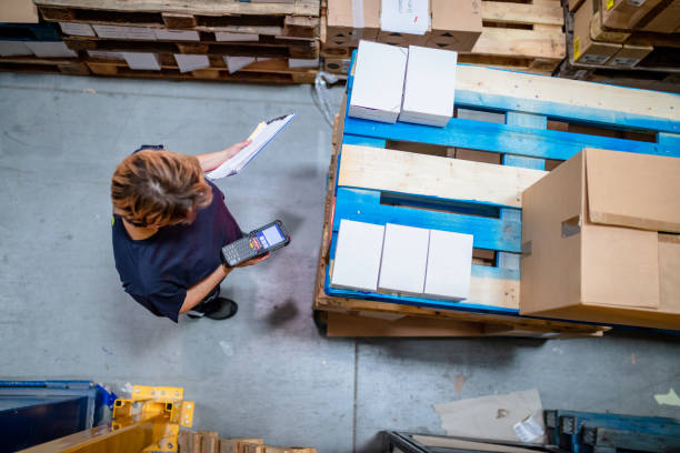 Areal view of woman amidst pallets in warehouse Areal view of woman with barcode reader and checklist amidst pallets in warehouse amidst stock pictures, royalty-free photos & images