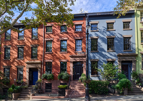 Brooklyn, NY - August 15, 2021: Areas of shadow from trees fall on three old brick houses on Joralemon St in Brooklyn Heights, NYC. Two houses are red and one is painted blue. The cobblestone street slopes downward to the left side of the photo.