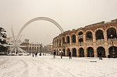 Verona, Italy - Dec 14, 2012: The Arena di Verona in winter with the comet while it snows (I-III century). UNESCO world heritage site. Veneto, Italy, Europe. A group of people strolls in the famous square, Piazza Brà.