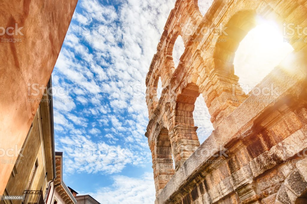 Arena of Verona, ancient roman amphitheater in Italy during sunrise and blue sky with clouds. - foto stock