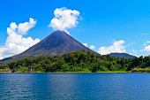 Arenal Volcano 'puffs' out a cloud above the rainforest on the shores of Lake Arenal in Costa Rica